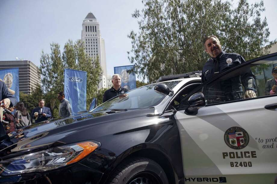 """Charlie Beck, chief of Los Angeles Police Department, stands next to the new Ford Police Responder hybrid vehicle during a Monday event outside of LAPD headquarters in Los Angeles. Ford says it expects its new Police Responder hybrid sedan, a modified Fusion, will become the first gasoline-electric cop car to be """"pursuit-rated,"""" meaning it can race through city streets while navigating crowded intersections or hopping curbs. Photo: Patrick T. Fallon /Bloomberg News / © 2017 Bloomberg Finance LP"""