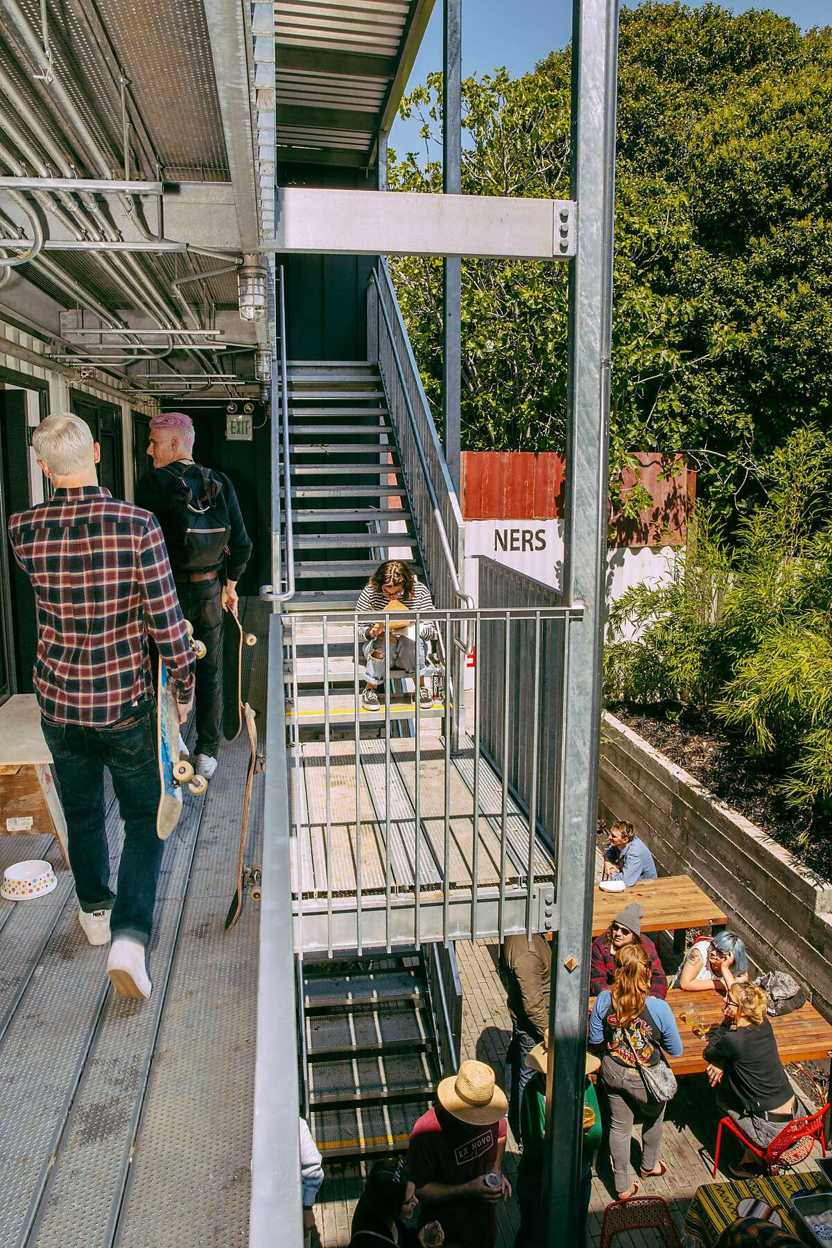 Patrons gather in the back yard and around the shops and studios at the MacArthur Annex in Oakland on April 9, 2017. Every second Sunday of the month Arthur Mac's and the Annex host an event with food, live music, and tarot readings.