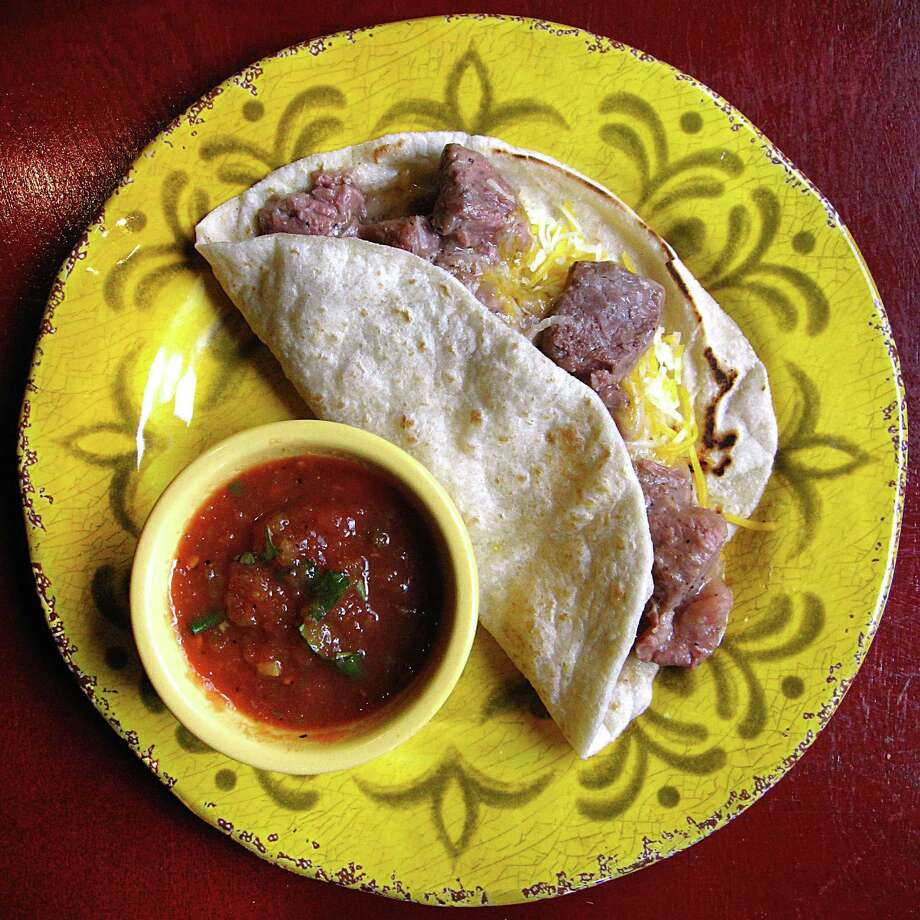 Carne guisada taco with cheese on a handmade flour tortilla from Karolina's Mexican Food on U.S. 281 South. Photo: Mike Sutter /San Antonio Express-News