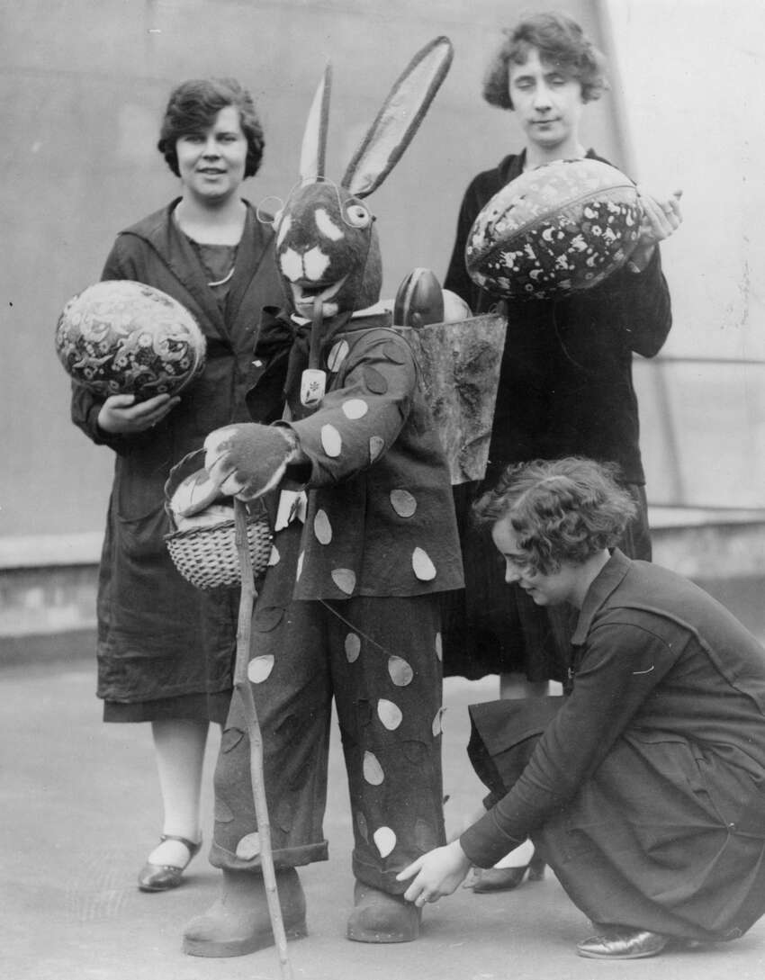 circa 1930: An Easter bunny carries easter eggs in a basket on his back while one woman adjusts his turn-ups and two others carry large easter eggs.