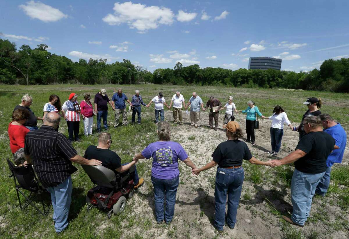 Friends and relatives of people buried in the Aldine Cemetery hold a prayer vigil at the cemetery. Crews with heavy equipment cleared the land of headstones and trees.