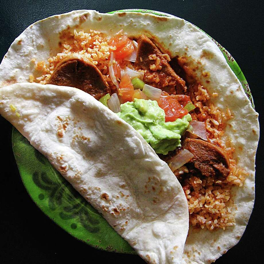 The Azteca super taco with lengua a la mexicana, rice and guacamole on a handmade flour tortilla from Rolando's Super Tacos on West Hildebrand Avenue. Photo: Mike Sutter /San Antonio Express-News
