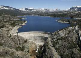 In this April 3 2017 photo, snow covering the Sierra Nevadas is seen in the background of the PG&E hydroelectric dam at Spaulding Lake in Nevada County, Calif. Gov. Jerry Brown declared an end to California's historic drought Friday, April 7, 2017, lifting emergency orders that had forced residents to stop running sprinklers as often and encouraged them to rip out thirsty lawns during the state's driest four-year period on record. (AP Photo/Rich Pedroncelli)