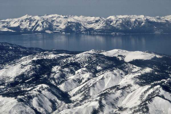 In this photo taken March 2, 2017, record winter snowfall is seen in the mountains around Lake Tahoe, in this aerial photo taken from above the Washoe Valley just south of Reno, Nev. Surveyors will crunch across the deepest mountain snowdrifts California has seen in years on Thursday, March 30, 2017, to take the first snow measurement of the spring, a time when the snow begins to melt and flow downhill. (AP Photo/Scott Sonner)