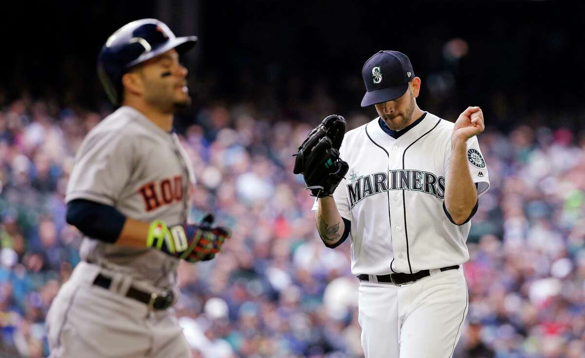 Seattle Mariners starting pitcher James Paxton, right, reacts to the final out of the first inning, a ground out by Houston Astros's Jose Altuve, left, in a baseball game Monday, April 10, 2017, in Seattle. The game is the home opener for the Mariners. (AP Photo/Elaine Thompson)