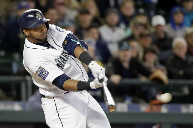 Seattle Mariners' Nelson Cruz singles in a pair of runs against the Houston Astros in the fifth inning of a baseball game Monday, April 10, 2017, in Seattle. The game is the home opener for the Mariners. (AP Photo/Elaine Thompson)