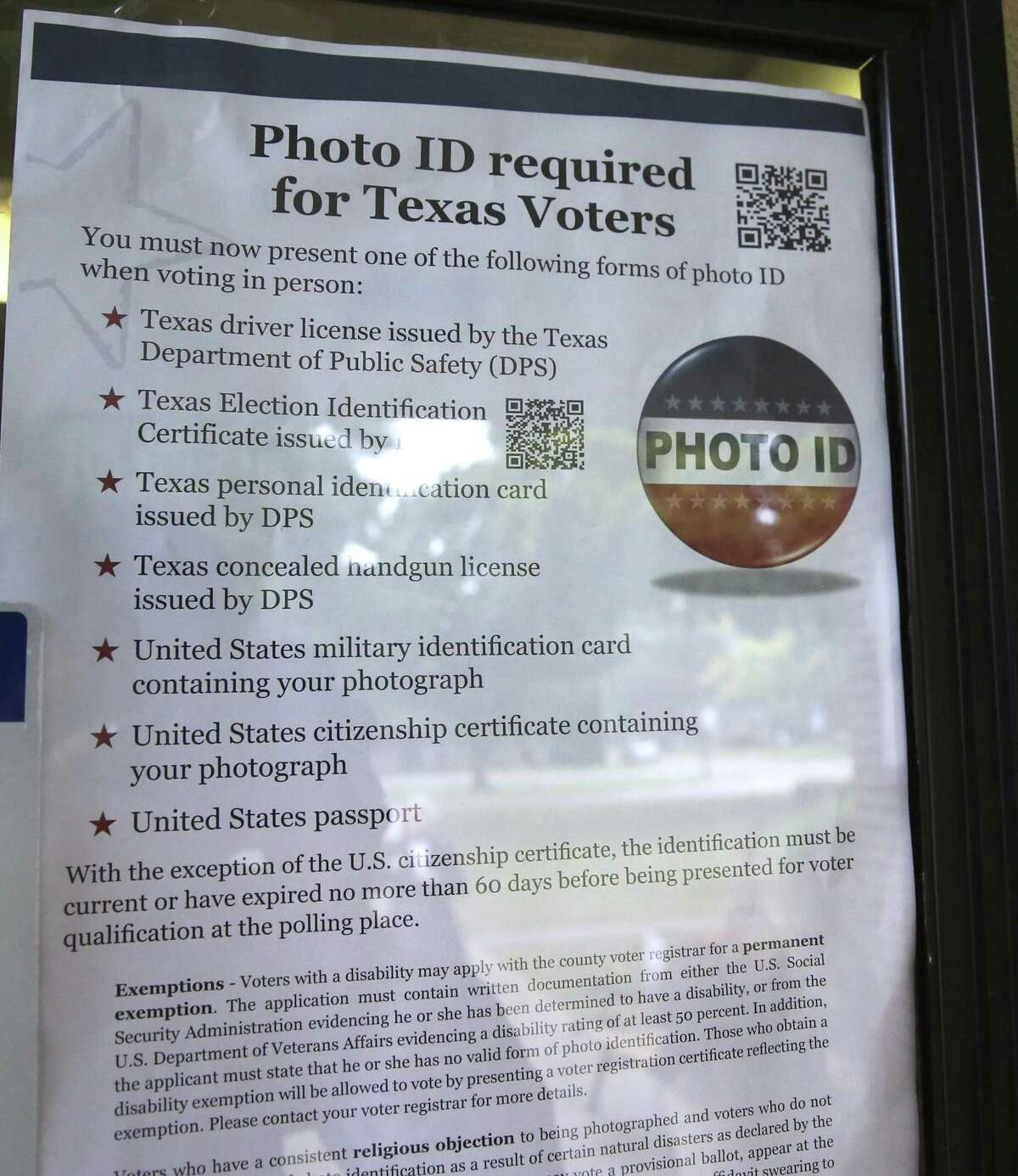 FILE - In this Nov. 5, 2013 file photo, a sign in a window tells of photo ID requirements for voting at a polling location in Richardson, Texas. A judge has ruled for a second time that Texas' strict voter ID law was intentionally crafted to discriminate against minorities.The ruling by U.S. District Judge Nelva Gonzales Ramos of Corpus Christi Monday, April 10, 2017, comes more than two years after she likened the ballot-box rules in Texas to a