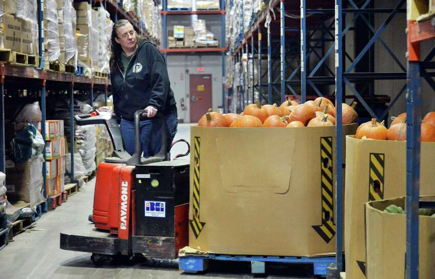 Food bank warehouse worker Tammie Racine stocks fresh farm produce collected through the