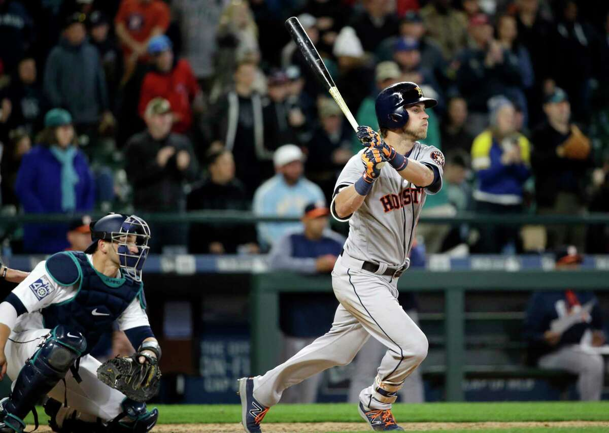 Houston Astros' Josh Reddick, right, and Seattle Mariners catcher Mike Zunino watch the path of Reddick's line drive to second end the baseball game, Monday, April 10, 2017, in Seattle. The Mariners won 6-0. (AP Photo/Elaine Thompson)