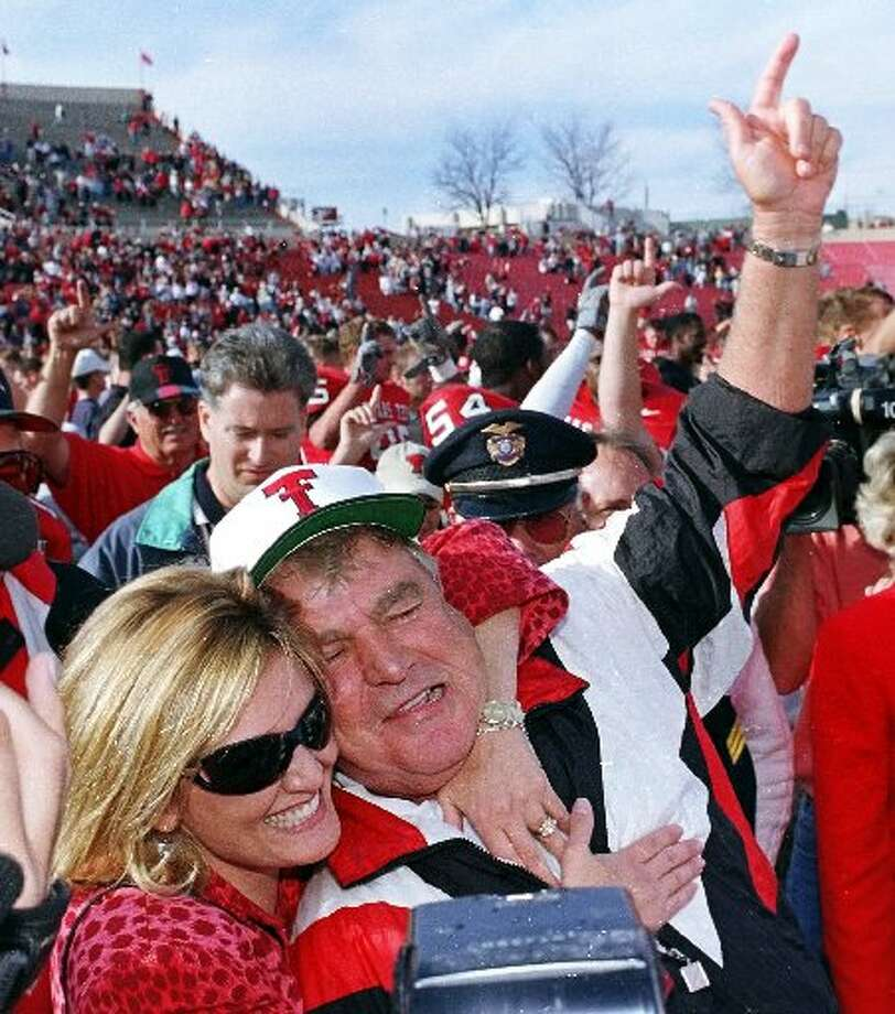 Texas Tech head coach Spike Dykes gets a hug from his daughter after the Red Raiders' victory Saturday November 20, 1999 over the Oklahoma Sooners in Lubbock. It was Dykes' last game as coach.(AP File Photo)
