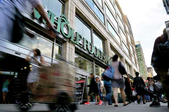 Pedestrians pass a Whole Foods Market in New York's Union Square. The Austin-based chain has been dealing wih its worst sales slump in more than a decade.