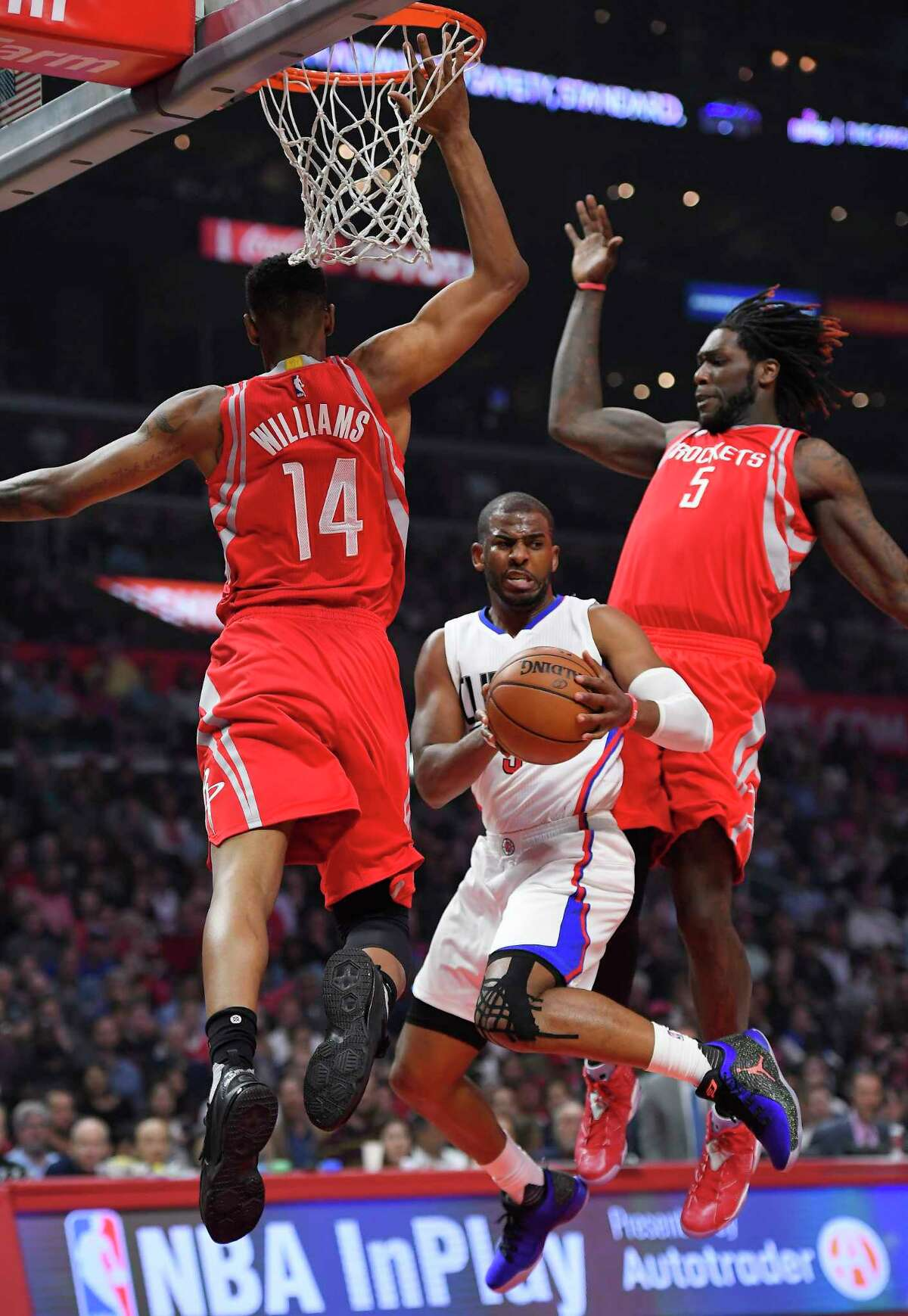Los Angeles Clippers guard Chris Paul, center, passes the ball while under pressure from Houston Rockets forward Troy Williams, left, and forward Montrezl Harrell during the first half of an NBA basketball game, Monday, April 10, 2017, in Los Angeles. (AP Photo/Mark J. Terrill)