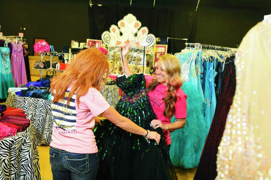 Manager Cassie Miller, left, volunteer Jennifer Giere check on the dresses on display at the Giving Gown Foundation's annual Boutique Day. The event was held at the Bammel Church of Christ Teen Center from April 6-9. The nonprofit foundation provides prom dresses teens who in need of assistance of providing a gown on their own. Photo: Tony Gaines, Photographer