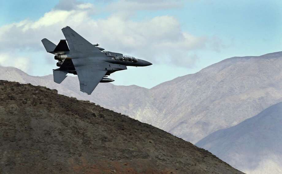 In this Feb. 27, 2017, photo an F-15E Strike Eagle from Seymour Johnson AFB in North Carolina flies out of the nicknamed Star Wars Canyon turning toward the Panamint range over Death Valley National Park, Calif. Military jets roaring over national parks have long drawn complaints from hikers and campers. But in California's Death Valley, the low-flying combat aircraft skillfully zipping between the craggy landscape has become a popular attraction in the 3.3 million acre park in the Mojave Desert, 260 miles east of Los Angeles. (AP Photo/Ben Margot) Photo: Ben Margot, STF / Associated Press / Copyright 2017 The Associated Press. All rights reserved.