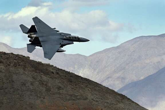 In this Feb. 27, 2017, photo an F-15E Strike Eagle from Seymour Johnson AFB in North Carolina flies out of the nicknamed Star Wars Canyon turning toward the Panamint range over Death Valley National Park, Calif. Military jets roaring over national parks have long drawn complaints from hikers and campers. But in California's Death Valley, the low-flying combat aircraft skillfully zipping between the craggy landscape has become a popular attraction in the 3.3 million acre park in the Mojave Desert, 260 miles east of Los Angeles. (AP Photo/Ben Margot)