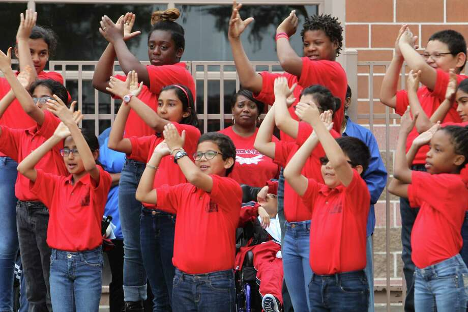Student with the Signing Chior perform during a rally for the announcement that Houston Texans Johnathan Joseph and UnitedHealthcare provided new playground equipment for children with disabilities at Houston Independent School District's T.H. Rogers School Tuesday, April 11, 2017, in Houston. The school's population includes pre-K through 12th grade students with multiple impairments and pre-K through 8th grade students with hearing impairments.  The playground equipment donation was made possible by a $11,000 donation from UnitedHealthcare to Joseph's Dreambuilders program. Joseph will join UnitedHealthcare leaders at the school to introduce the new equipment to hundreds of students. Photo: Steve Gonzales, Houston Chronicle / © 2017 Houston Chronicle