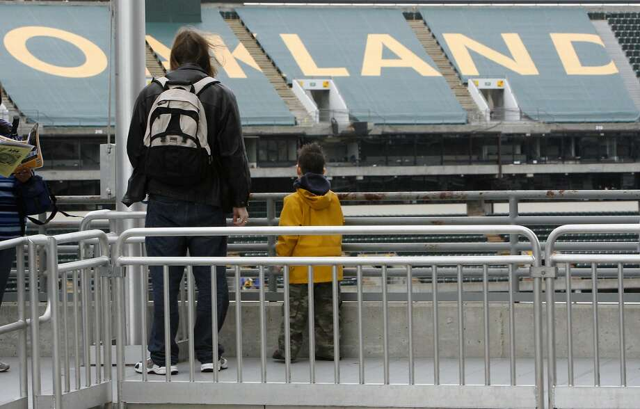 Alan Kemmer and his son Michael check out the tarps covering the third deck seating area that team officials will put up to shrink capacity this season. The annual Oakland A's Fanfest at McAfee Coliseum in Oakland, Calif. on 1/28/06. PAUL CHINN/The Chronicle  Ran on: 01-29-2006   Ran on: 01-29-2006   Ran on: 01-29-2006   Ran on: 01-29-2006 Photo: PAUL CHINN, SFC