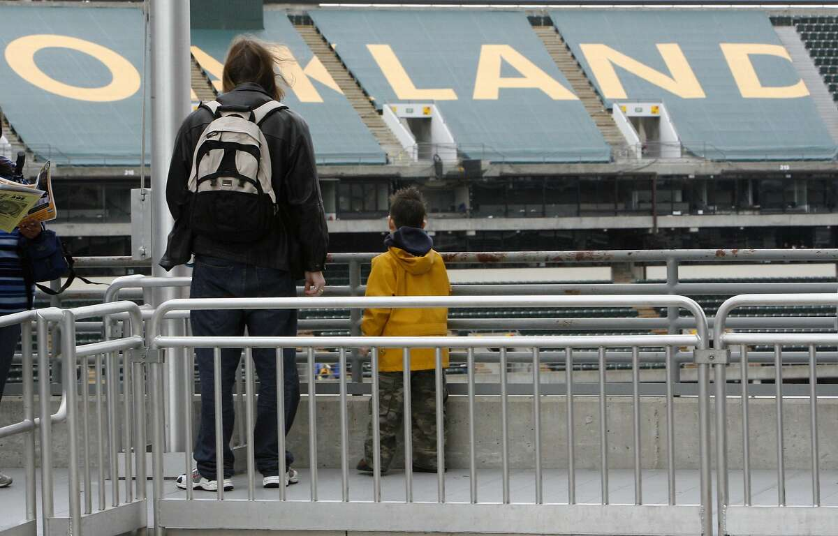 Alan Kemmer and his son Michael check out the tarps covering the third deck seating area that team officials will put up to shrink capacity this season. The annual Oakland A's Fanfest at McAfee Coliseum in Oakland, Calif. on 1/28/06. PAUL CHINN/The Chronicle Ran on: 01-29-2006 Ran on: 01-29-2006 Ran on: 01-29-2006 Ran on: 01-29-2006