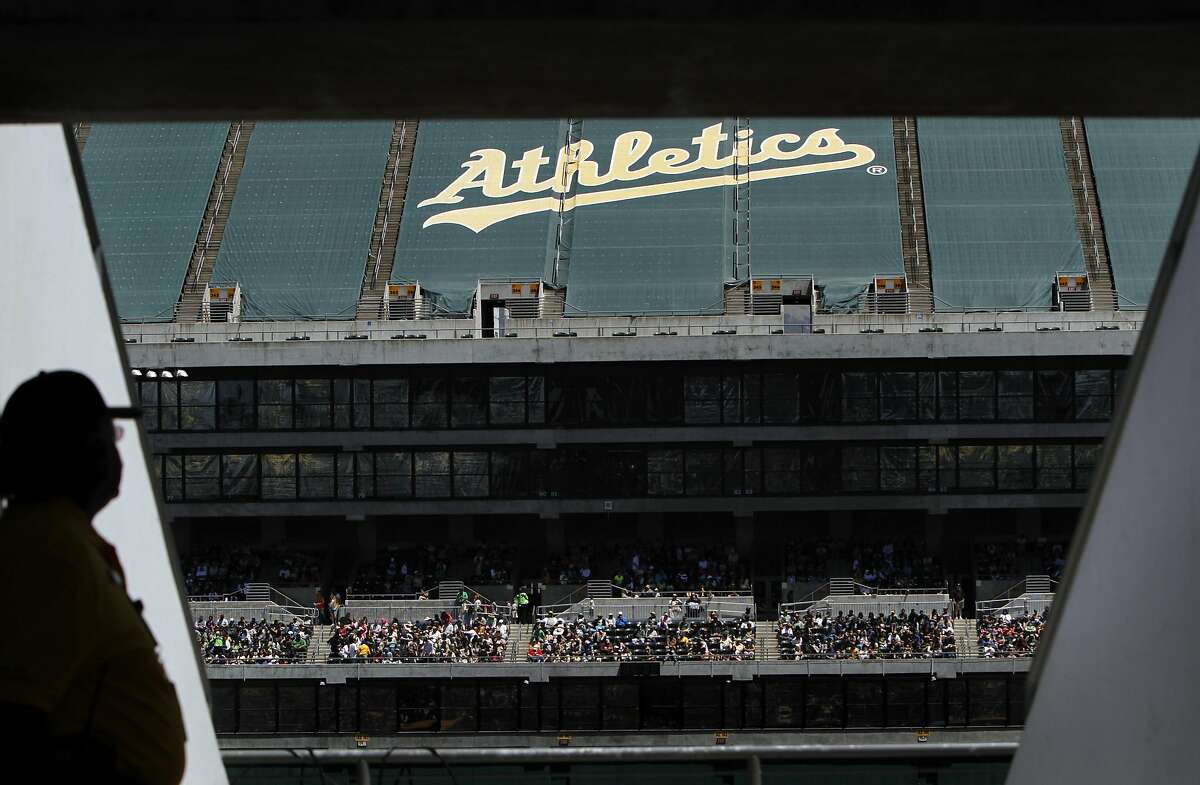 The majority of the upper bowl at the O.Co Coliseum has been closed to fans, and the seats are covered with green tarps painted with the team name. A security guard watches the game from the only open sections, above home plate, during the Oakland A's game against the Blue Jays in Oakland, Calif., Wednesday, May 9, 2012.