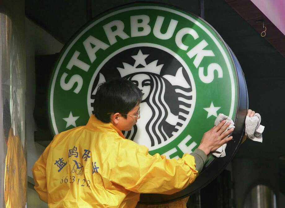 """Window cleaners wipe a Starbucks sign in Beijing. Starbucks says it will begin offering a """"critical illness insurance plan"""" to its eligible full-time employees in stores operated by the company in China. The benefit will cover employees' parents for 30 illnesses as well as some surgeries. Photo: AFP /Getty Images File Photo / AFP or licensors"""