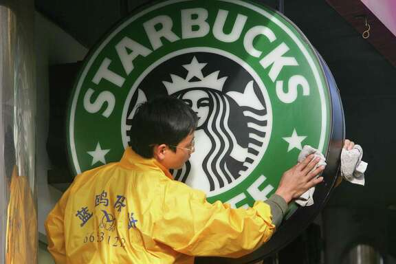 """Window cleaners wipe a Starbucks sign in Beijing. Starbucks says it will begin offering a """"critical illness insurance plan"""" to its eligible full-time employees in stores operated by the company in China. The benefit will cover employees' parents for 30 illnesses as well as some surgeries."""