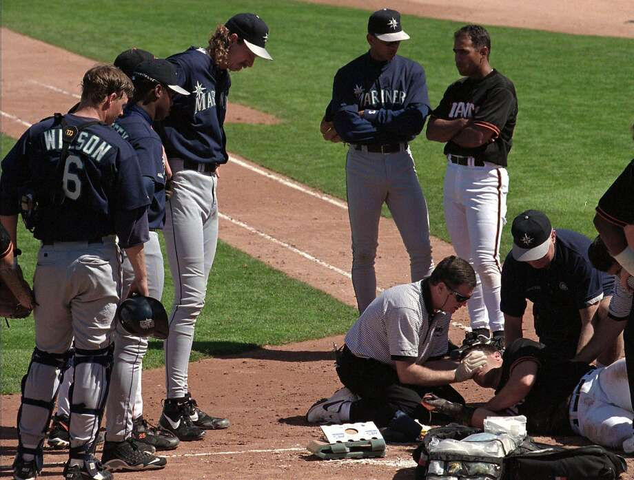 San Francisco Giants trainer Mark Letendre tends to injured Giants batter J.T. Snow who was struck by a pitch thrown by Seattle Mariners pitcher Randy Johnson, third from left, during the second inning of their spring training game in Scottsdale, Ariz., Tuesday March 11, 1997.  Snow was hit in the arm and head and was taken to a nearby hospital.  The game was delayted 29 minutes before an ambulance took Snow off the field.(AP Photo/Kevork Djansezian) Photo: KEVORK DJANSEZIAN, Associated Press
