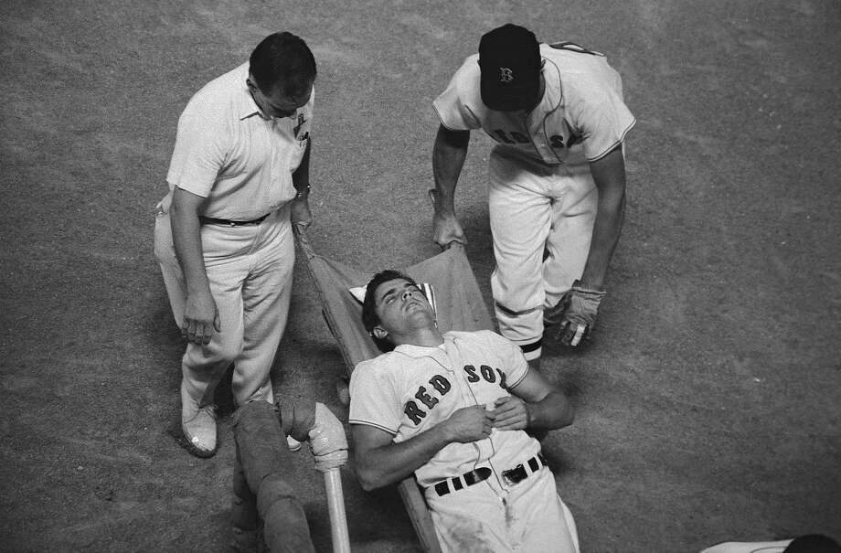 (Original Caption) Boston Red Sox right fielder Tony Conigliaro is carried off the field unconscious by trainer Buddy Leroux and an unidentified teammate in the fourth inning of the Red Sox-Angels game here on 8/18. Tony was hit by a Jack Hamilton pitch and suffered a concussion. Photo: Bettmann, Bettmann Archive