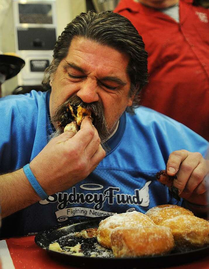 Marcus Bartone, of Derby, digs in to a plate of paczkis, or Polish filled doughnuts, during the 19th annual Paczki Eating Contest at Eddy's Bake Shop in Ansonia in February. Photo: Brian A. Pounds / Hearst Connecticut Media / Connecticut Post