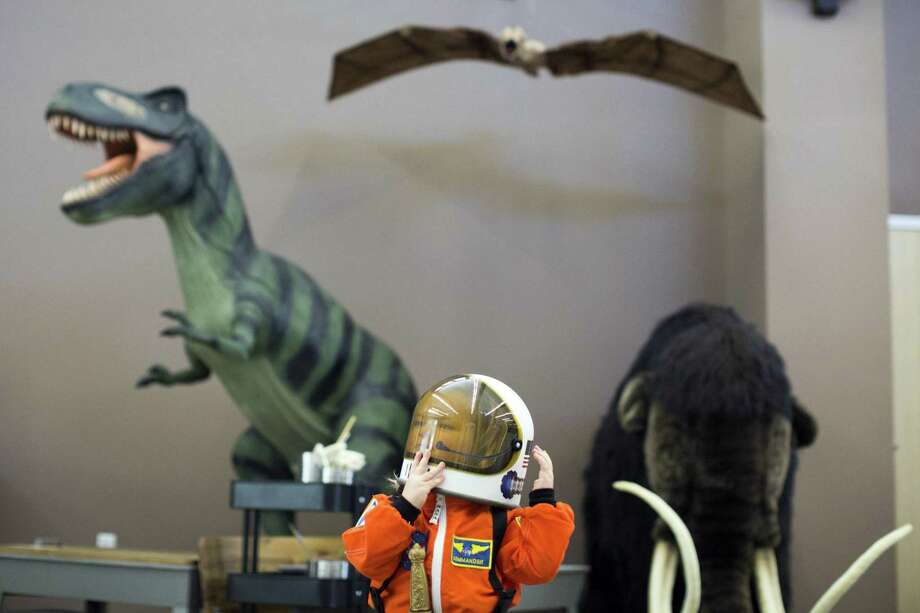 Presli Atkinson, 3, adjusts her helmet after storytime at Hondo's new library. The facility opened to celebration after much turmoil. Photo: Ray Whitehouse /For The San Antonio Express-News