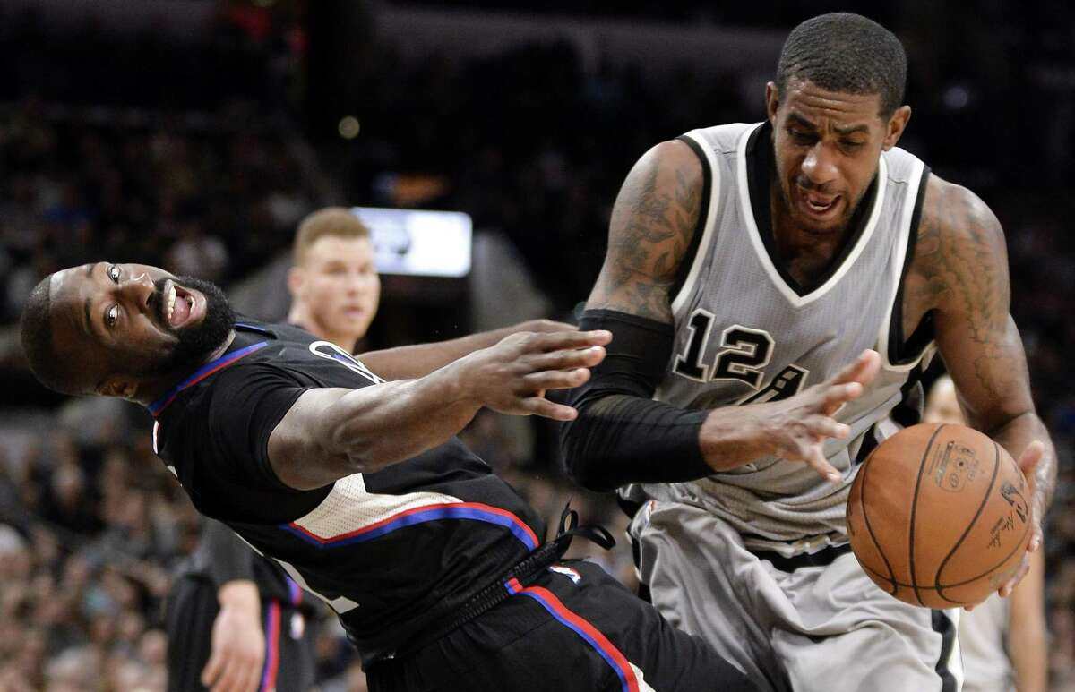 Los Angeles Clippers guard Raymond Felton falls after colliding with Spurs forward LaMarcus Aldridge, who was called for the offensive foul, during the second half on April 8, 2017, in San Antonio.