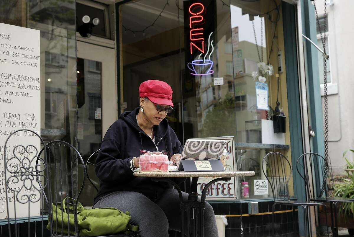 PHD student Adeeba Deterville works on her dissertation outside the Good News Cafe in Oakland, Calif. on Tues. April 11, 2017.