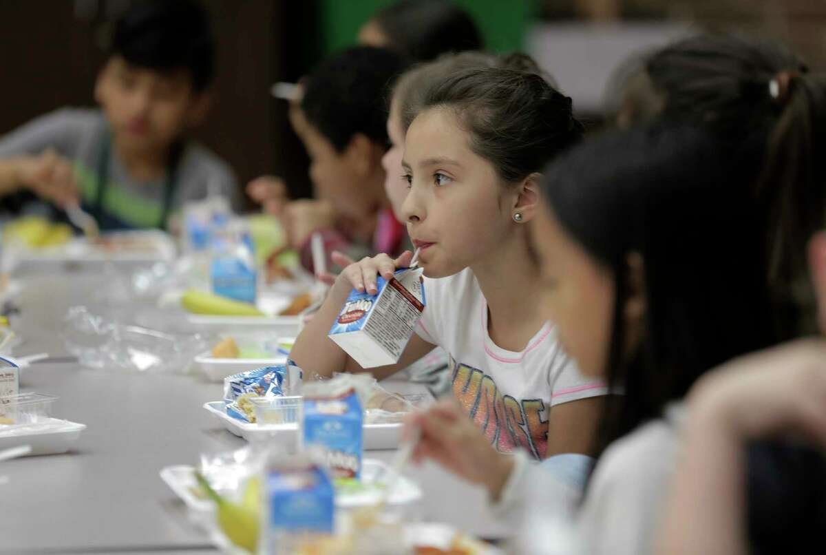 Fourth grader Mia Acuna drinks her milk with her classmatesat Hancock Elementary School eat lunch on Thursday, April 6, 2017, in Houston. The school offers a program where parents can put extra money in the funds so students who forget their lunch money get a full meal.