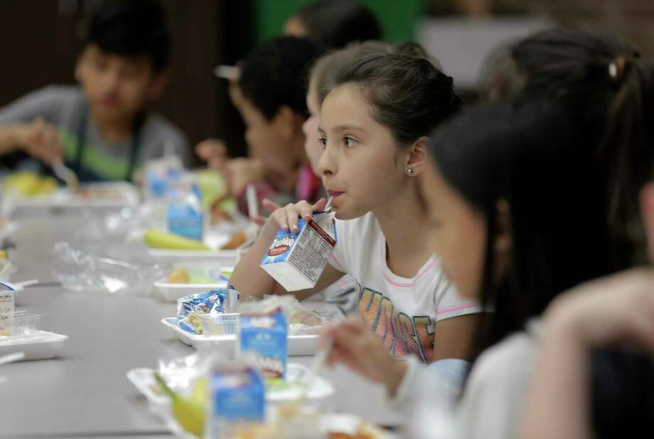 Fourth grader Mia Acuna drinks her milk with her classmatesat Hancock Elementary School eat lunch on Thursday, April 6, 2017, in Houston. The school offers a program where parents can put extra money in the funds so students who forget their lunch money get a full meal. Photo: Elizabeth Conley, Houston Chronicle / © 2017 Houston Chronicle