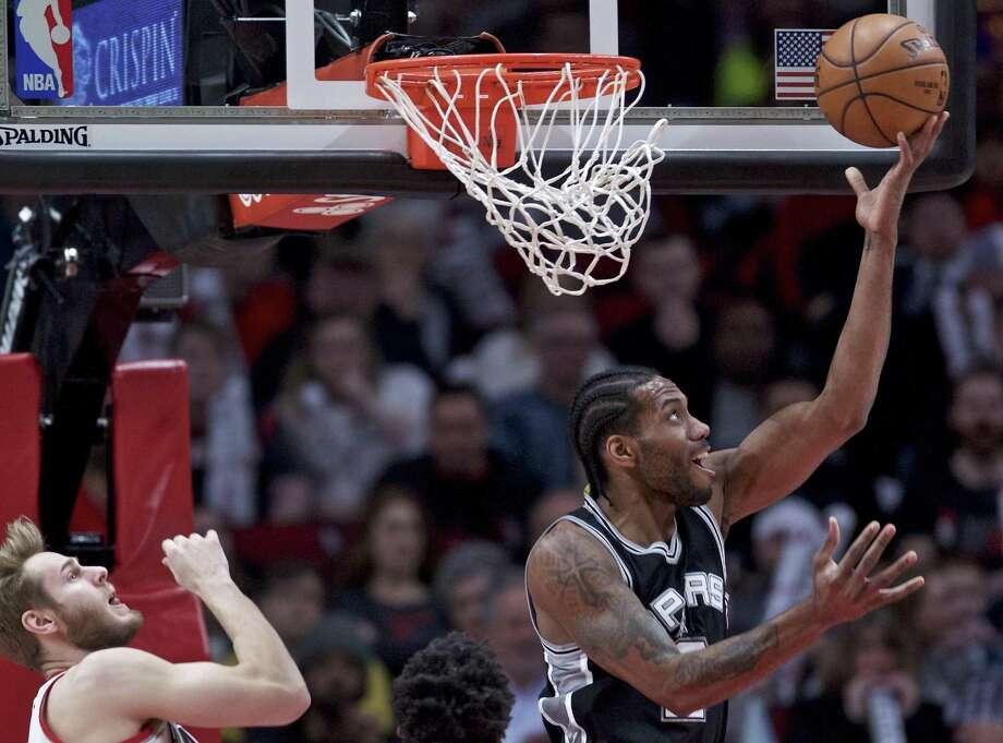 Spurs forward Kawhi Leonard shoots after getting past Trail Blazers forward Jake Layman during the first half in Portland, Ore., on April 10, 2017. Photo: Craig Mitchelldyer /Associated Press / FR170751 AP