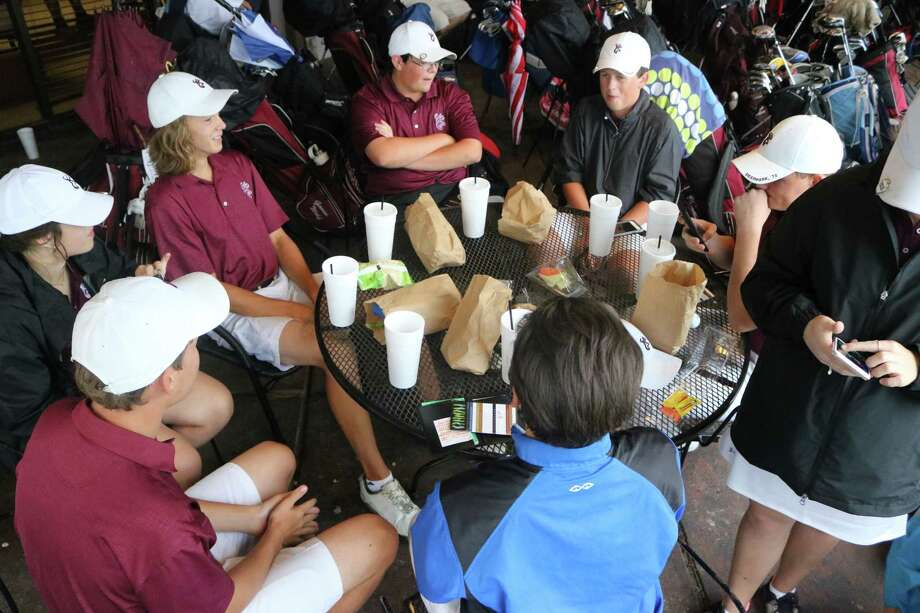 Members of the Deer Park II team plus medalists relax at the Clear Creek Golf Course clubhouse while watching the rain wash out the final nine holes to the first day of the 22-6A tournament. Photo: Robert Avery