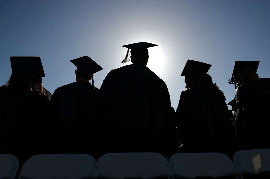 In this June 18, 2014 file photo, high school graduates stand and sing during graduation ceremonies in Santa Ana, Calif. Photo: Mark Felix, Associated Press