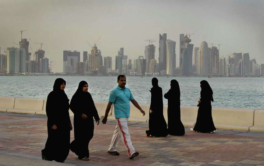 "FILE- In this Saturday, April 7, 2012 file photo, with the new high-rise buildings of downtown Doha in the background, Qatari women and a man enjoy walking by the sea, in Doha, Qatar. A Qatari has made a $2 million payment to a Greek shoe salesman's firm in America to help it get ""proof of life"" and ultimately free ruling family members kidnapped in Iraq. The payment is the latest development in the abduction saga that began in December 2015. The payment, on file with the U.S. government, suggests Qatar's government is trying to be as transparent as it can in the hostage negotiation after earlier facing allegations it funded extremists. (AP Photo/Kamran Jebreili, File) Photo: Kamran Jebreili, STF / Copyright 2017 The Associated Press. All rights reserved."