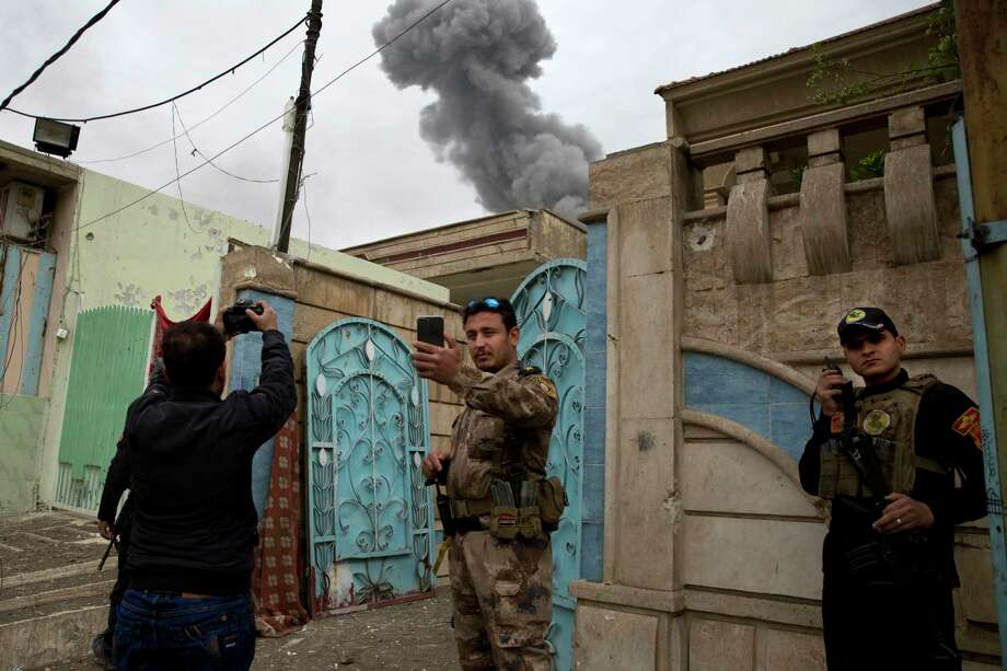 An Iraqi special forces lieutenant takes a selfie with the plume from an airstrike, during heavy fighting in the Yarmouk district of western Mosul, Iraq, Tuesday, April 11, 2017. (AP Photo/Maya Alleruzzo) ORG XMIT: XMA101 Photo: Maya Alleruzzo / Copyright 2017 The Associated Press. All rights reserved.