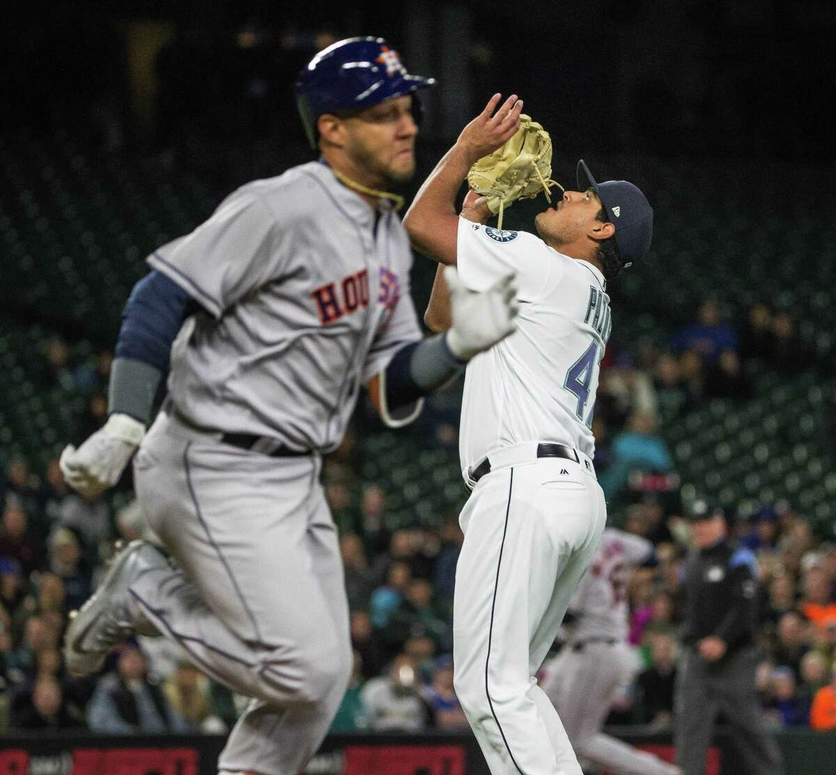 Seattle Mariners reliever James Pazos waits for a high bouncer by the Houston Astros' Yuli Gurriel to come down in the sixth inning at Safeco Field in Seattle on Tuesday, April 11, 2017. The throw to first was too late to get Gurriel.