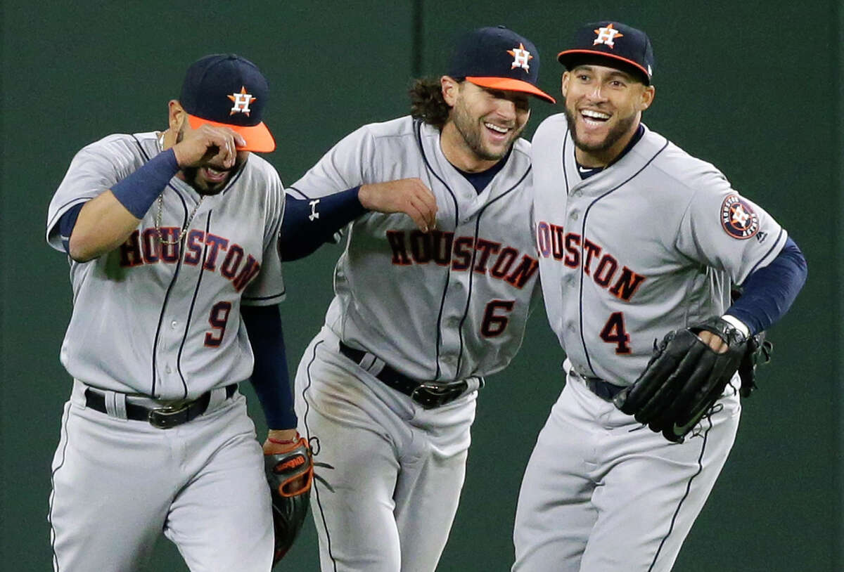 Houston Astros outfielders Marwin Gonzalez, (9) Jake Marisnick (6) and George Springer (4) celebrate after the Astros beat the Seattle Mariners 7-5 in a baseball game, Tuesday, April 11, 2017, in Seattle. (AP Photo/Ted S. Warren)
