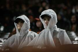 Giants fans watch the 9th inning of a game between the San Francisco Giants and the Arizona Diamondbacks in the rain at AT&T Park in San Francisco, California, on Tuesday, April 11, 2017.