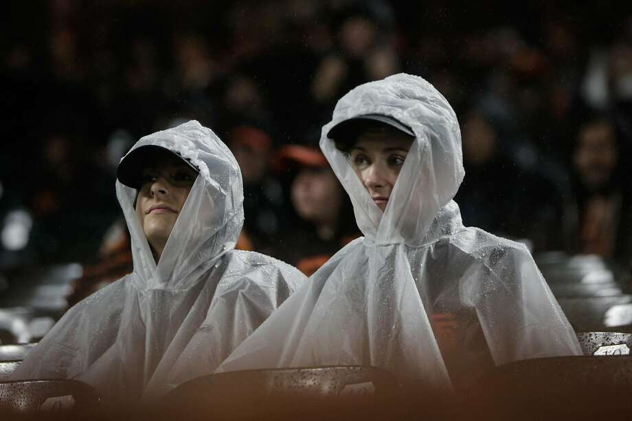 Giants fans watch the 9th inning of a game between the San Francisco Giants and the Arizona Diamondbacks in the rain at AT&T Park in San Francisco on April 11. Photo: Gabrielle Lurie, The Chronicle