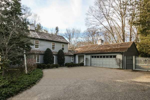 The gray colonial farmhouse at 280 Verna Hill Road, sits on a 0.70-acre level property at the corner of Hillside Road in the Greenfield Hill neighborhood. It has an attached two-car garage.