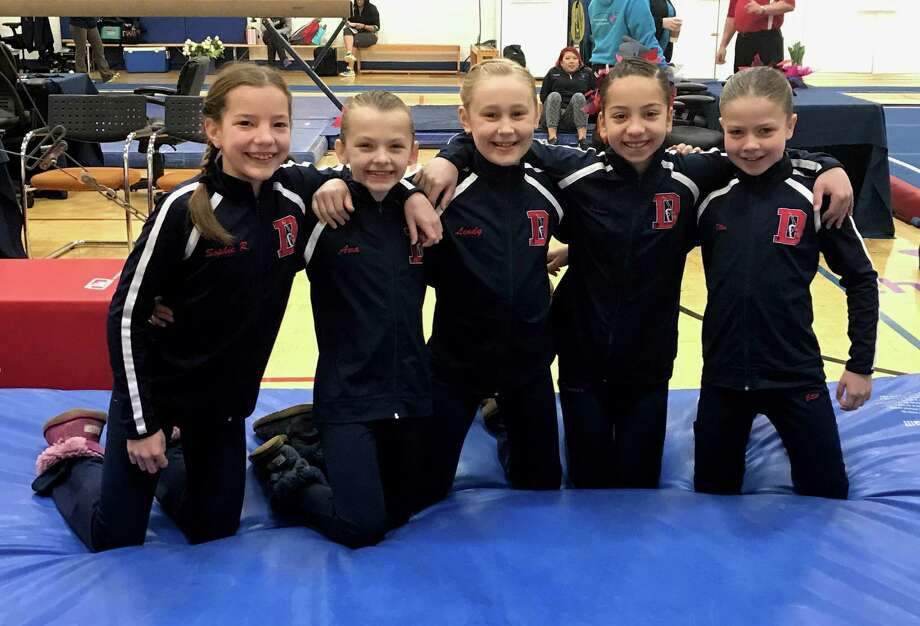 Sophie Root and Ava Licata of New Canaan and their Darien YMCA gymnastics teammates Lindy Mueller, Tanner Generoso and Ellie Davies showed their team spirit before the Connecticut YMCA State Championship meet. Photo: Contributed Photo / Darien News contributed