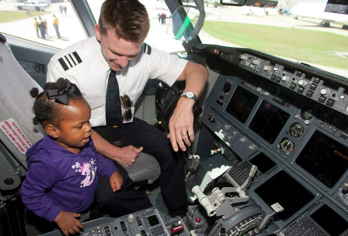 Southwest Airline's First Officer Dan Jensen shows Kenadee Josey around the cockpit of a Boeing 737-700 series during the HobbyFest at Hobby Airport.