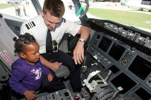 Southwest Airline's First Officer Dan Jensen shows Kenadee Josey around the cockpit of a Boeing 737-700 series during the Hobby Fest at Hobby Airport.
