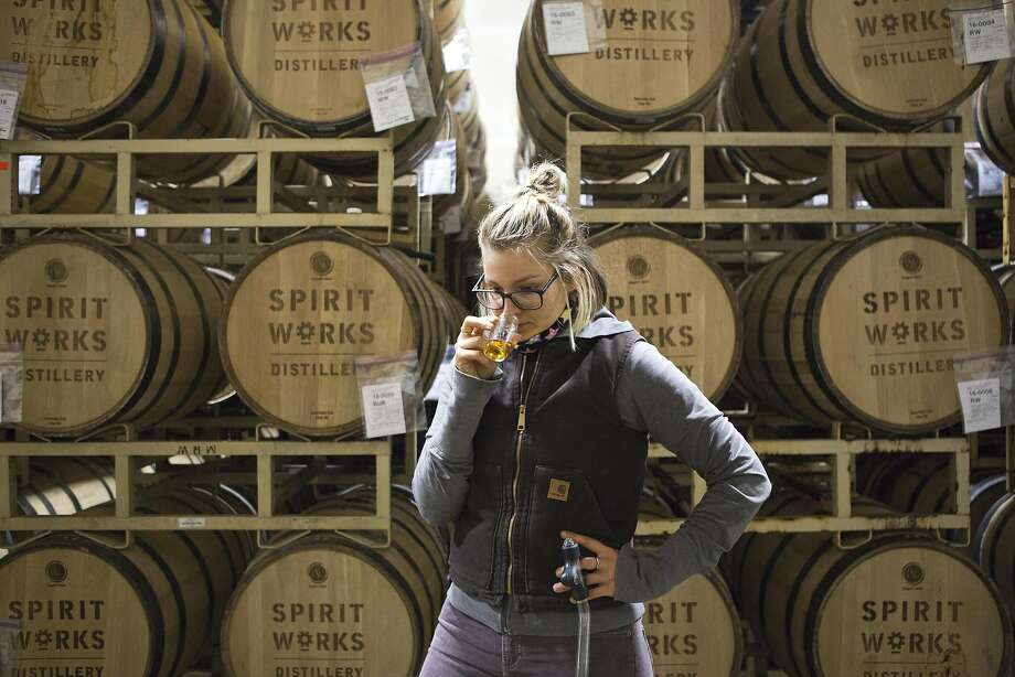 Lauren Patz pulls a sample of bourbon that's been aging in the barrels at Spirit Works. Photo: Vivian Johnson, Special To The Chronicle