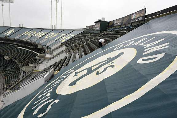 Workers with contractor Images Outdoor remove the tarps covering seating on the upper deck at Oakland Alameda County Coliseum in Oakland, CA, on Wednesday April 12, 2017.