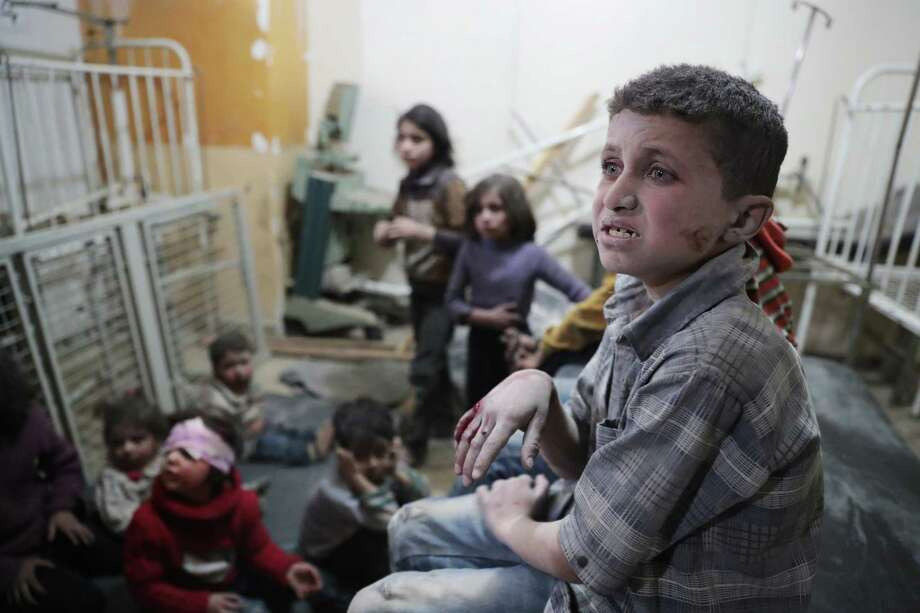 TOPSHOT - Syrian children wait to receive treatment at a makeshift clinic following reported air strikes by government forces in the rebel-held town of Douma, on the eastern outskirts of Damascus, on April 4, 2017. / AFP PHOTO / Abd DoumanyABD DOUMANY/AFP/Getty Images Photo: ABD DOUMANY, Stringer / AFP or licensors