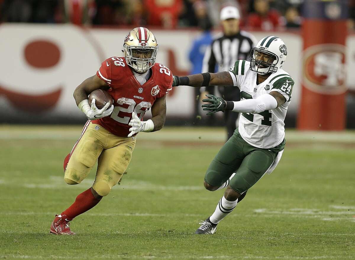 San Francisco 49ers running back Carlos Hyde (28) runs against New York Jets cornerback Darrelle Revis (24) during overtime of an NFL football game in Santa Clara, Calif., Sunday, Dec. 11, 2016. (AP Photo/Ben Margot)